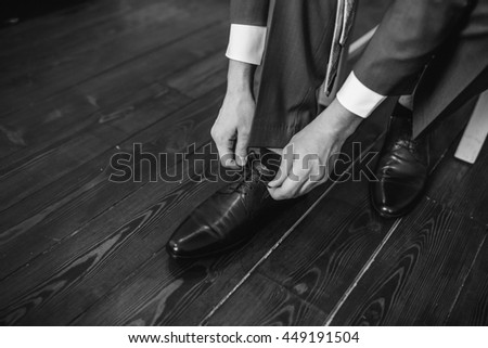 Business man dressing up with classic, elegant shoes. Groom wearing shoes on wedding day, tying the laces and preparing. Black and white photo - stock photo