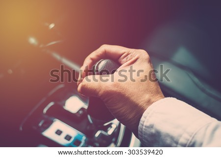 Business man driver hand shifting the gear stick. Vintage filter - stock photo