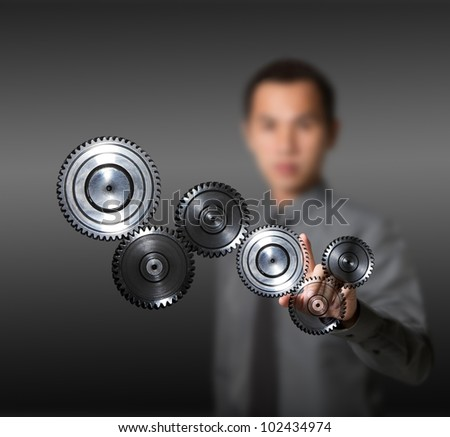 business man driving set of gears - concept of industry, machine, teamwork, power, and advance - stock photo