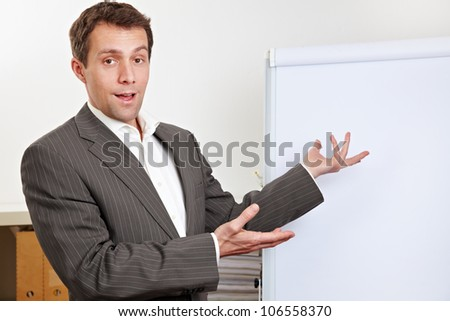 Business man during presentation pointing to white flipchart - stock photo