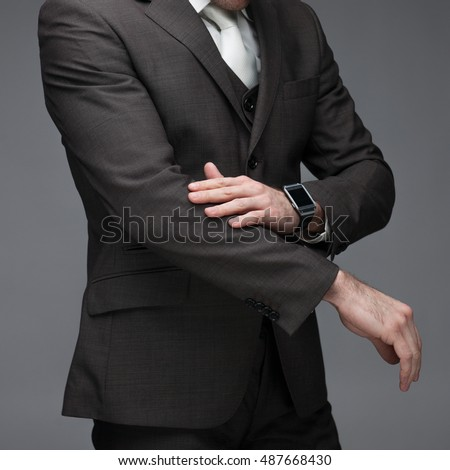 Business man dusting of his sleeves, on a grey background, stock picture