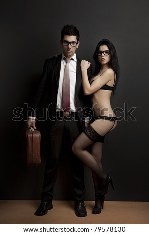 Business man embraced with a sexy young woman in lingerie. Concept about work and pleasure - stock photo
