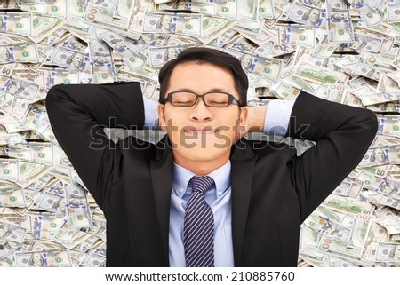 business man enjoying and lying on the money - stock photo