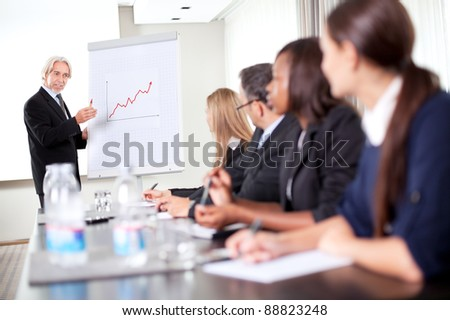 Business man explaining to his sales team about achieving preset targets - stock photo