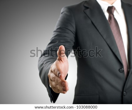 Business man extending hand to shake - stock photo