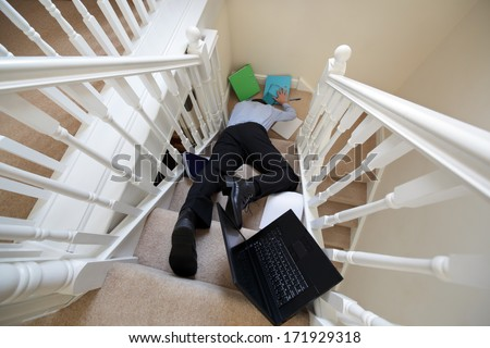 Business man falling down the stairs in the office concept for accident and insurance injury claim at work - stock photo