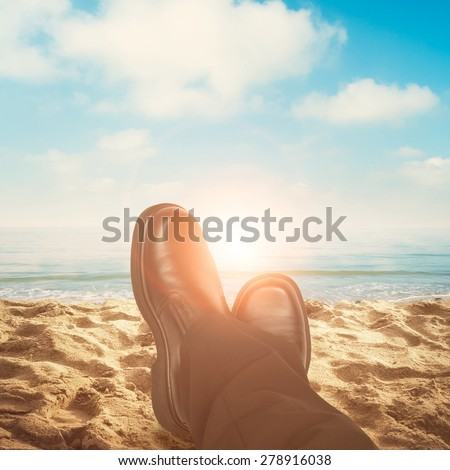 Business man feet relaxing at the beach - stock photo