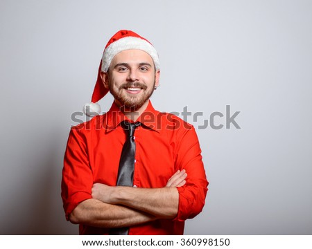Business man folded his arms crosswise. Winter, corporate party, Christmas hat isolated portrait of a man on a gray background, studio photo. - stock photo