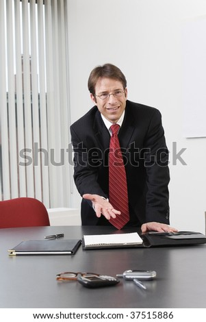 Business man gesturing in an office. - stock photo