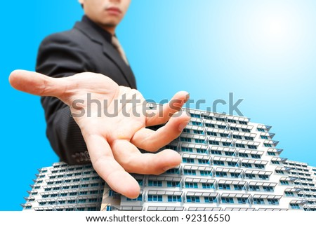 Business man give the hand on building - stock photo