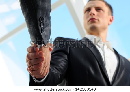 Business man giving a handshake to close the deal - stock photo