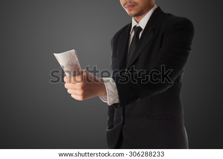 Business man giving money  on black background