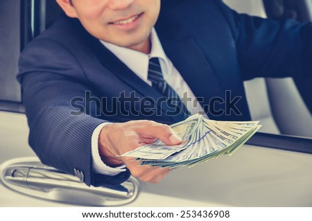 Business man giving money (US dollar bills) while sitting in a car; car insurance, sale & rental concepts - vintage (retro) style color effect - stock photo