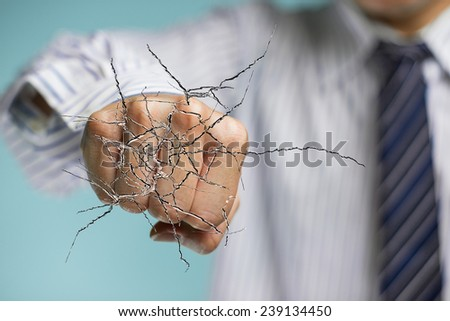 Business man hand hitting the transparent glass with cracked  - stock photo