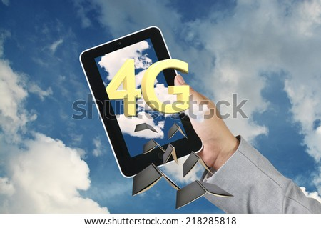 """Business Man Hand Hold Tablet get the word of """"4g""""  with Cloud and Blue sky and Book - stock photo"""