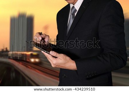Business man hand hold tablet on camera zoom abstract electric train and sunset light background as communication and transportation concept.