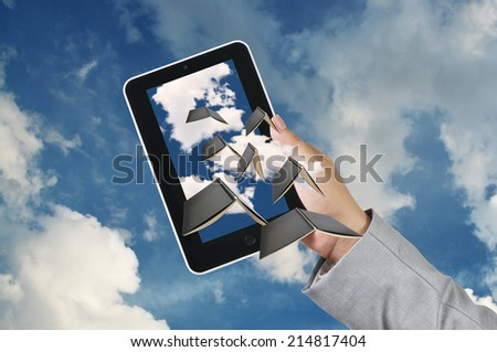 Business Man Hand hold Touch screen Tablet receive Flying Book as Cloud computing concept - stock photo