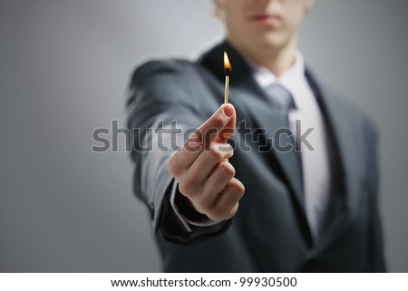Business man hand holding a burning match - stock photo