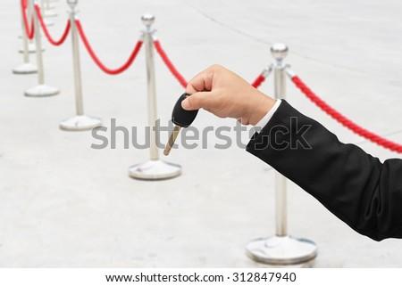 business man hand holding car key  - stock photo