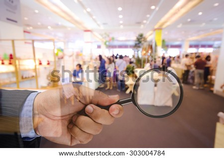 business man hand holding magnifier searching something , business concept - stock photo