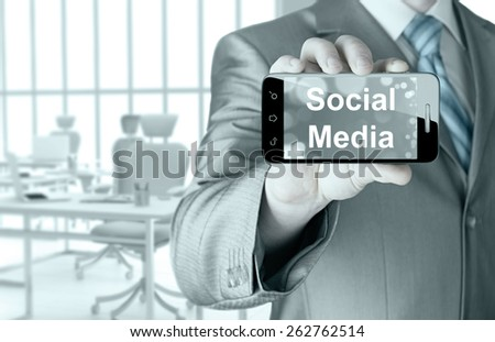 business man hand holding smartphone with Socail Media - stock photo