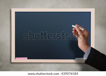 Business man hand holding white chalk with blank black chalkboard on concrete wall. Blank copyspace for your text or design.  - stock photo