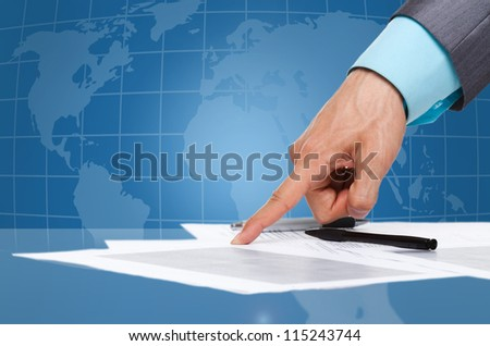 business man hand in elegant suit point finger at the document, paper on the desk over digital globe map background, sign up contract Concept of global international business collaboration - stock photo