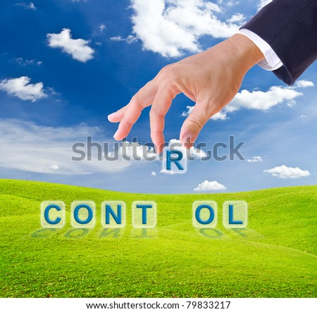 business man hand made control word buttons on green grass meadow - stock photo