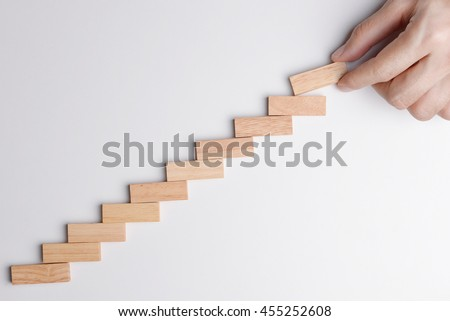 Business man hand put wood block on the top of statistics graph to keep raising up or growing business.  Top view on gray desk background.