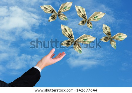 business man hand release origami butterfly from 100 dollar bill - stock photo
