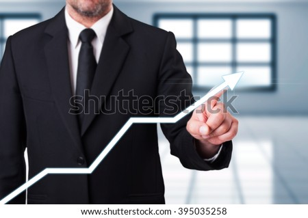 Business man hand touching a white increasing arrow as economic earnings concept - stock photo