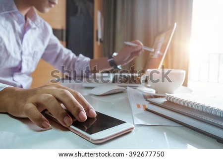 business man hand working and smart phone and laptop on office desk at office in morning light - stock photo