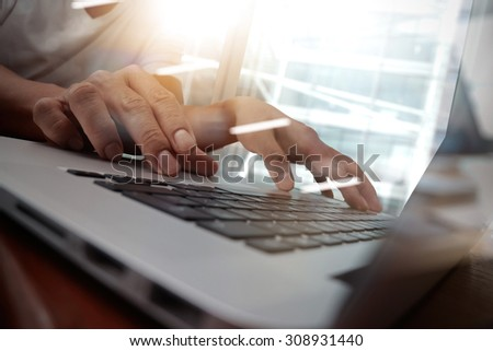 business man hand working on laptop computer on wooden desk as concept, young man student typing on computer sitting at wooden table - stock photo