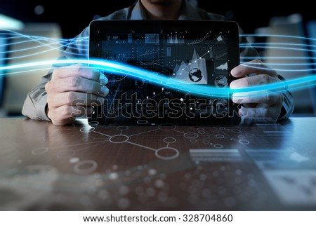 business man hand working on laptop computer with digital layer business strategy and social media diagram on wooden desk - stock photo