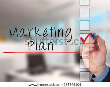 Business man hand  writing marketing plan concept and ticking check list. Isolated on office background. Stock Image - stock photo