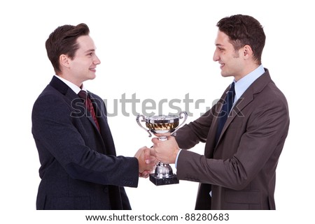 business man handing a trophy to his winning coleague and handshake him - stock photo