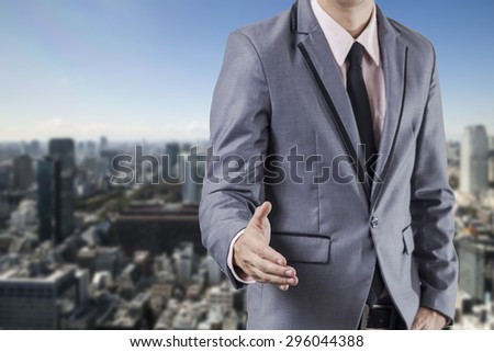 Business man handshake on business building background - stock photo