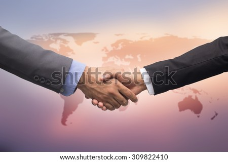 business man handshake over map on blurred blue sky backgrounds, business hands concept - stock photo