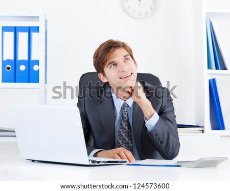 business man happy smile think look up sitting at office desk, handsome young businessman ponder, idea, hold hand finger on chin - stock photo