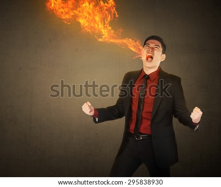 Business man having fire breath come from his mouth - stock photo