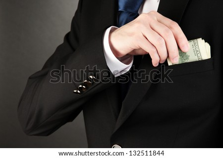 Business man hiding money in pocket on black background - stock photo