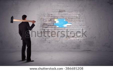 Business man hitting grungy brick wall with hammer - stock photo