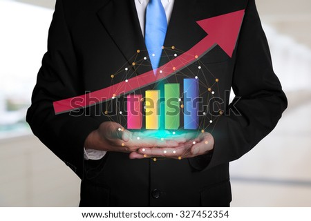 Business man hold a growing graph - stock photo