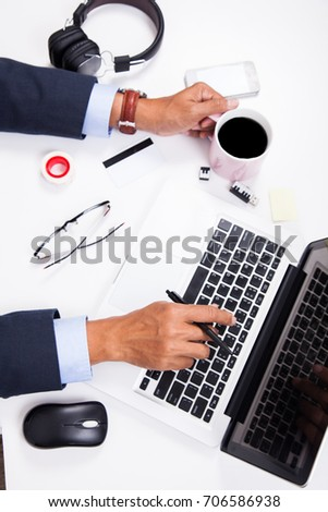 Business man hold coffee cup and working on laptop in office.