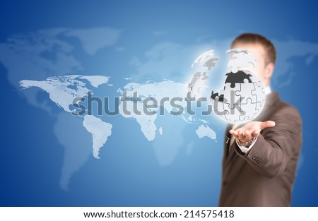 Business man hold exploding ball of gray puzzle pieces - stock photo