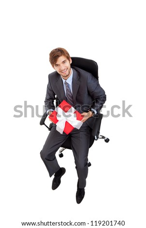 Business man hold gift box in chair, businessman give red present, sitting in armchair, happy smile, top angle view full length portrait isolated over white background - stock photo