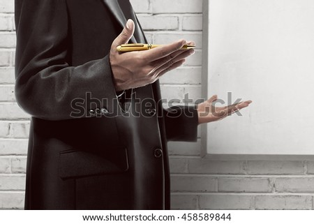 Business man hold pen with explaining gesture - stock photo