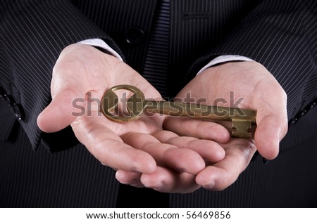 Business man holding a a golden key - stock photo