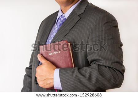 Business man holding a Bible in the place of work. Man who acts in the business world according to godly principles.