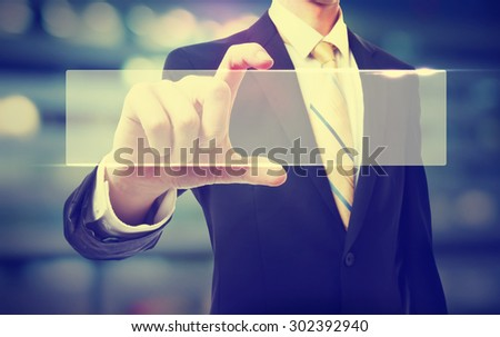 Business man holding a blank button on blurred cityscape background  - stock photo